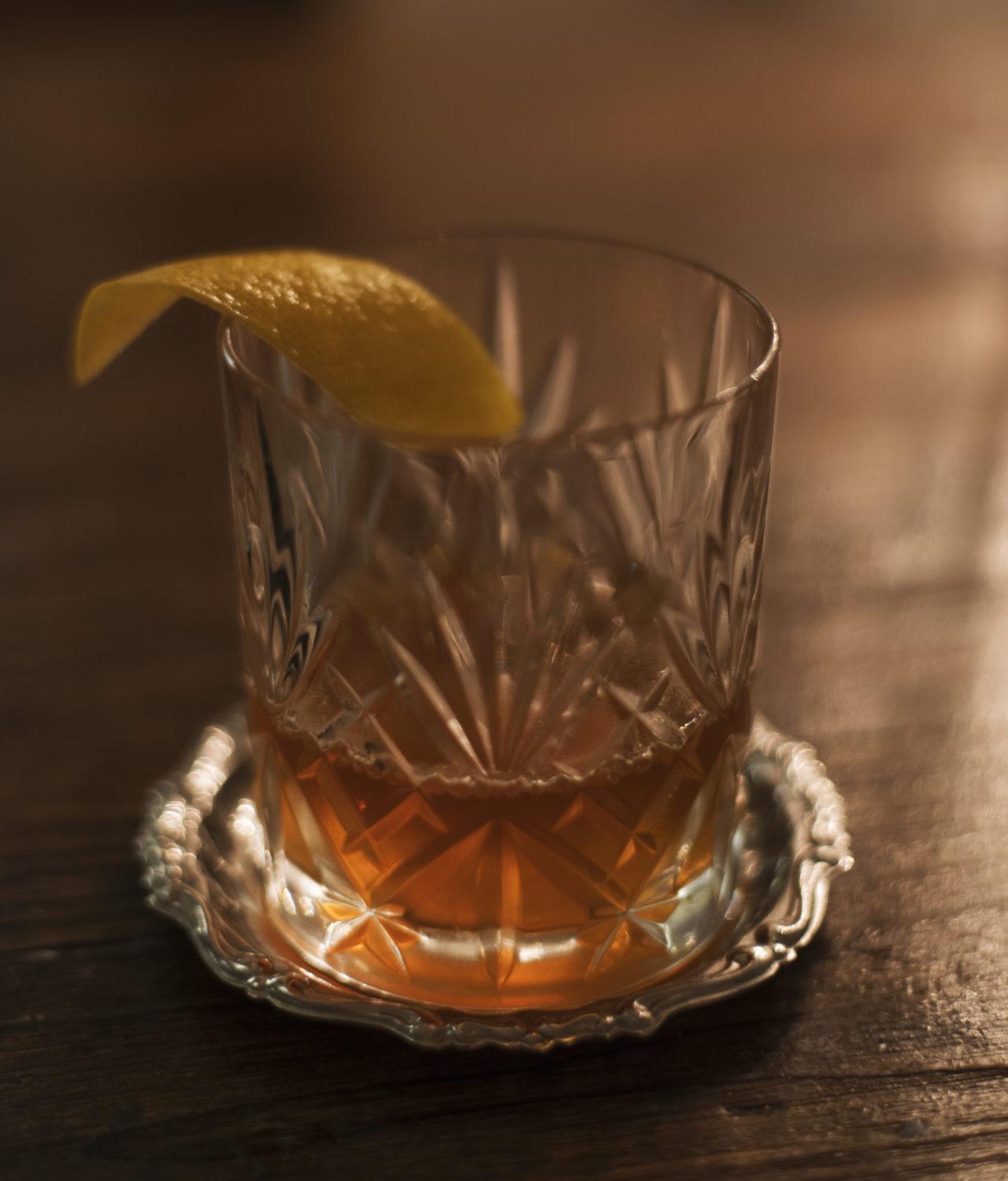bicchiere di cocktail sazerac con zest di limone servito su un coaster d'argento