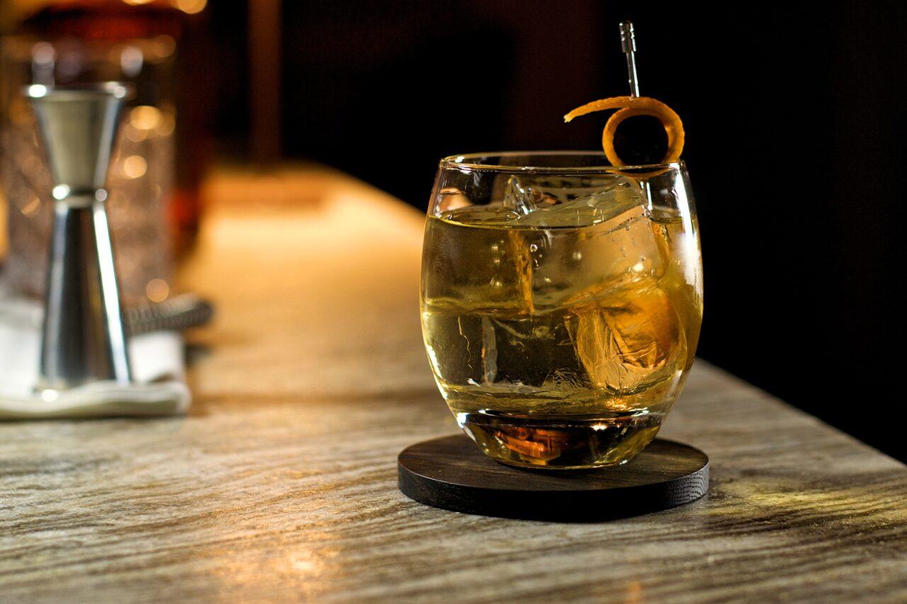 bicchiere tondo con ghiaccio gristallino e un cocktail con vodka e amaretto, sullo sfondo un jigger e una bottiglia di disaronno